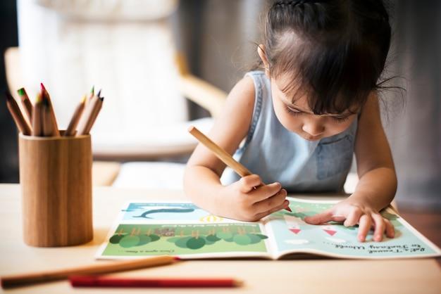 Petite fille dessinant un livre