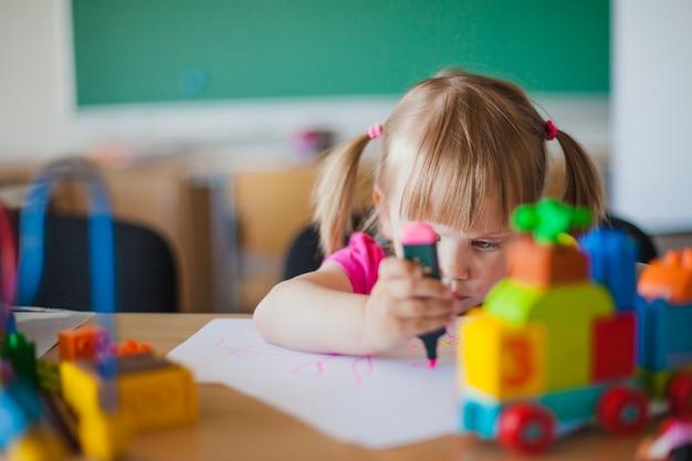 Une petite fille dessinant sur papier dans la salle de classe
