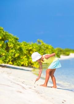 Petite fille dessinant sur la plage de sable fin