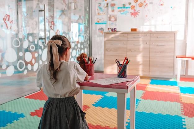 Petite fille dessinant avec un stylo de couleur en papier sur une table dans la salle de jeux, concept de bébé sain et préscolaire.