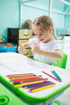 Petite fille dessine assise à une table dans une pièce sur fond de mur