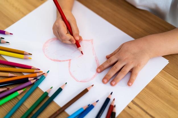 Petite fille dessine un coeur rouge