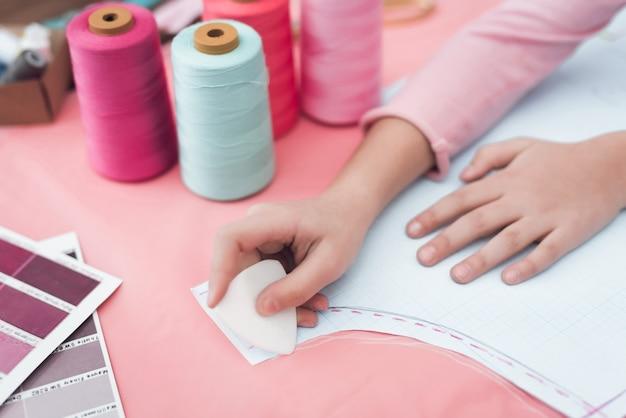 Petite fille dessine une craie sur le tissu.