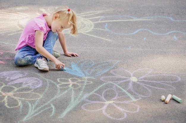 Petite fille dessine à la craie sur le trottoir