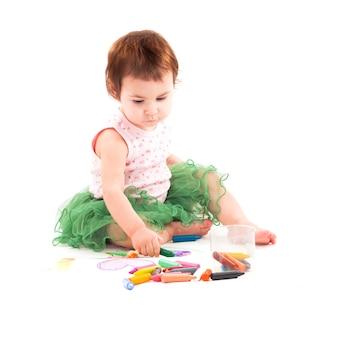 La petite fille dessine avec des crayons de cire sur le papier