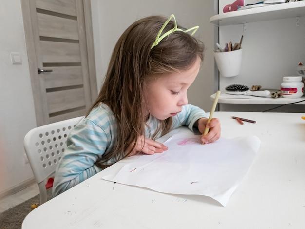 Petite fille dessine avec des crayons de couleur avec sa main gauche