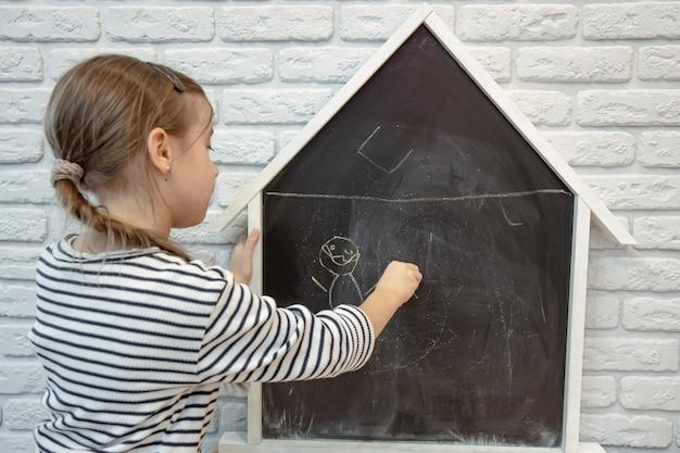 Une petite fille dessine un dessin à la craie sur un tableau noir en forme de maison.