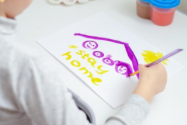 Une petite fille dessine une famille sous un toit avec des mots restez à la maison à l'aquarelle sur une feuille de papier blanc. restez à la maison concept.