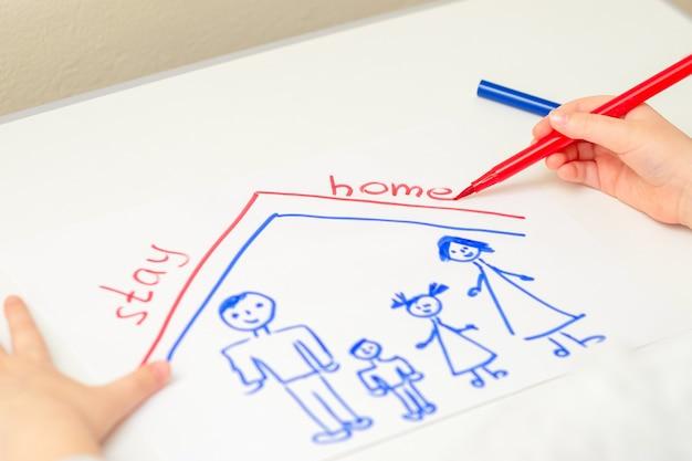 Une petite fille dessine une famille sous un toit avec des mots restez à la maison au stylo feutre sur une feuille de papier blanc. restez à la maison concept. mise au point sélective.
