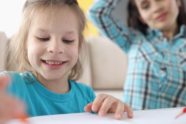 La petite fille dessine sur le papier à côté de la mère