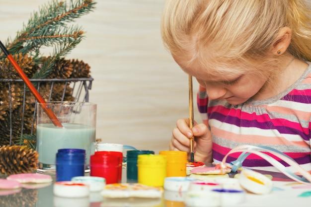 La petite fille dessine s'asseyant à la table