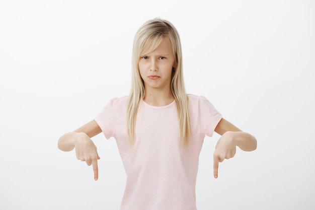 La petite fille déteste faire la vaisselle. portrait d'une jeune fille mignonne dégoûtée mécontente aux cheveux blonds, pointant vers le bas et fronçant les sourcils, étant offensée, exprimant l'aversion et l'ennui sur le mur gris