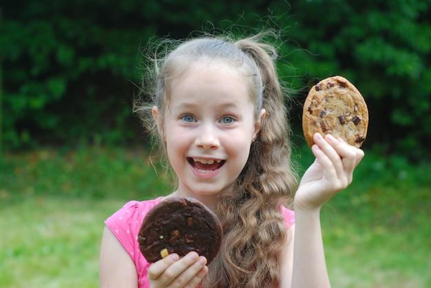 Petite fille avec deux biscuits nourriture malsaine pour les enfants.