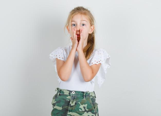 Petite fille disant quelque chose de confidentiel en t-shirt blanc