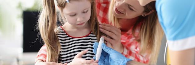 La petite fille a le docteur prenant le test sanguin avec la lancette
