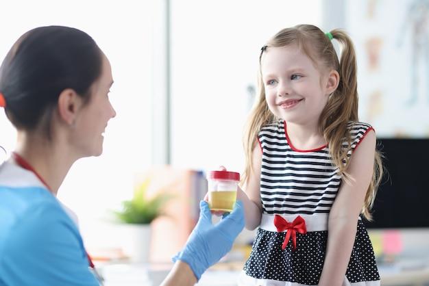 Petite fille donnant un pot d'urine à une infirmière en clinique