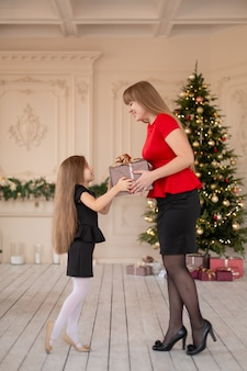 Petite fille donne à sa maman une boîte avec un cadeau de noël.