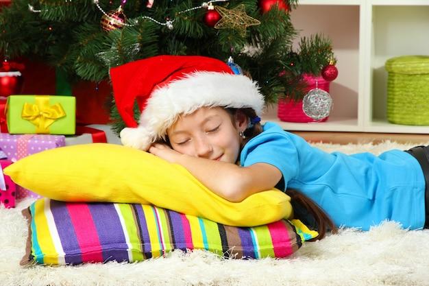 Petite fille dormant près de l'arbre de noël