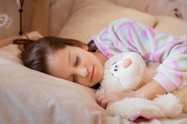 Petite fille dormant avec son jouet préféré