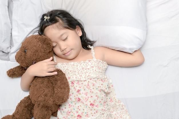 Petite fille dorment avec ours en peluche sur le lit