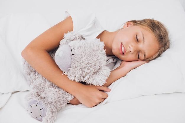 Petite fille dort avec son ours en peluche
