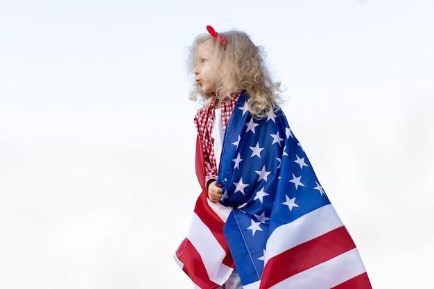 Une petite fille avec un drapeau américain sur fond blanc, le concept de patriotisme et le jour de l'indépendance des états-unis. journée des anciens combattants américains.