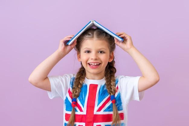 Une petite fille avec un drapeau anglais sur son t-shirt tient un livre sur la tête.