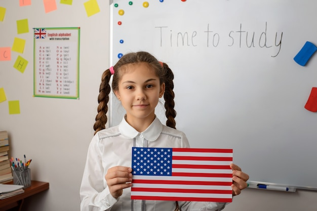 Petite fille avec le drapeau des états-unis à la leçon d'études de pays racontant les états-unis à ses camarades de classe