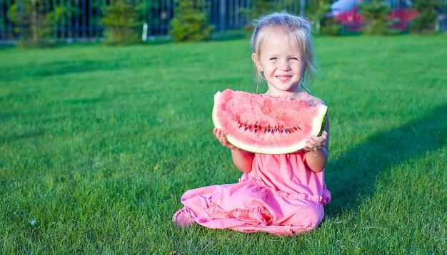 Petite fille drôle adorable avec un morceau de melon d'eau dans les mains