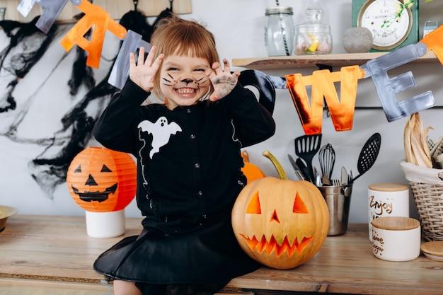 Petite fille drôle assise à côté de la citrouille et montrant un geste effrayant. halloween