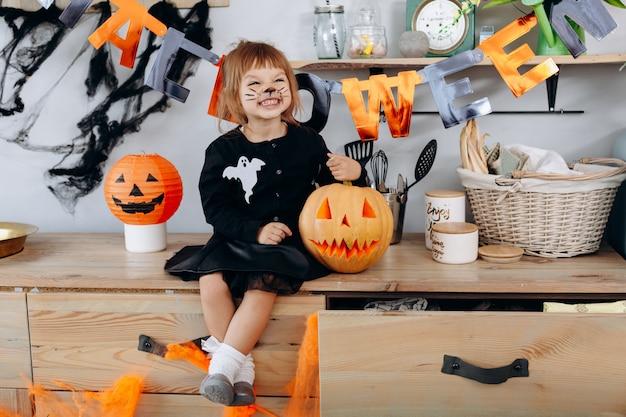 Petite fille drôle assise à côté de la citrouille et souriant joyeusement. halloween