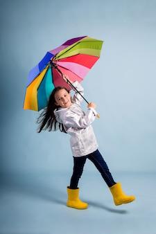 La petite fille drôle dans des bottes en caoutchouc et avec un parapluie multicolore est emportée par le vent sur un fond bleu avec une copie de l'espace