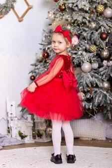 La petite fille drôle dans une robe rouge se tient près de l'arbre de noël