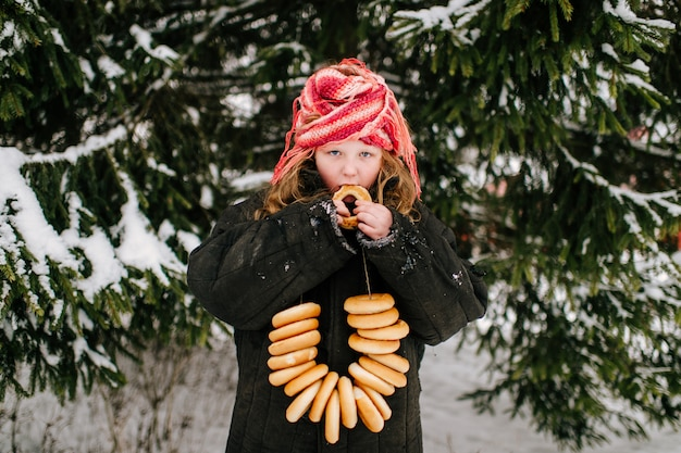 Petite fille drôle dans des vêtements adultes surdimensionnés manger des bagels sur la neige en journée d'hiver. fête traditionnelle du pays russe célébrant