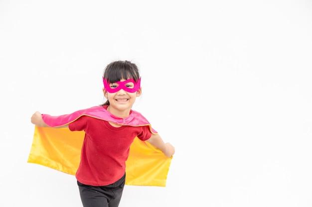 Petite fille drôle jouant le super-héros de puissance sur fond blanc. concept de super-héros.