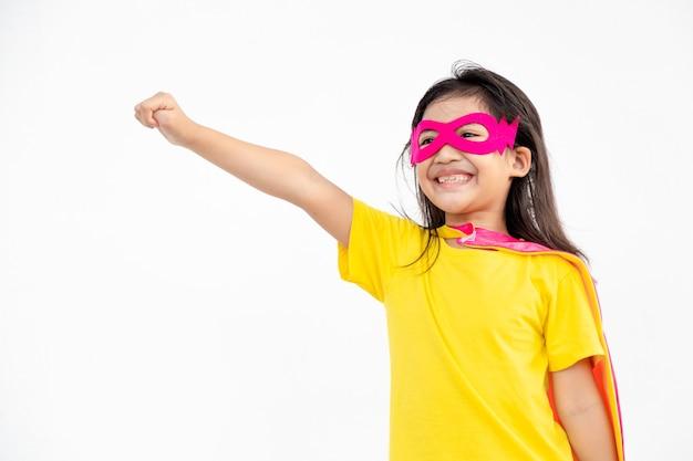 Petite fille drôle jouant le super héros de puissance sur fond blanc. notion de super-héros.