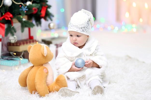 Petite fille drôle avec le jouet de noël près de l'arbre de noël