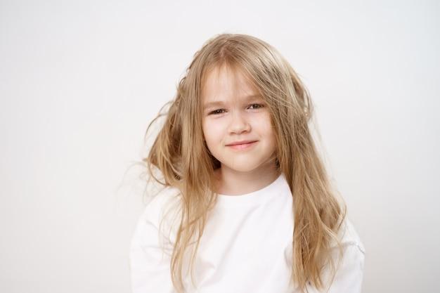 Petite fille drôle et mignonne aux cheveux longs hirsutes sur fond blanc. shampooing et baume pour enfants. cosmétiques pour filles. brossage léger.