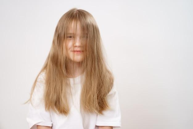 Petite fille drôle et mignonne avec son visage couvert de longs cheveux sur le blanc