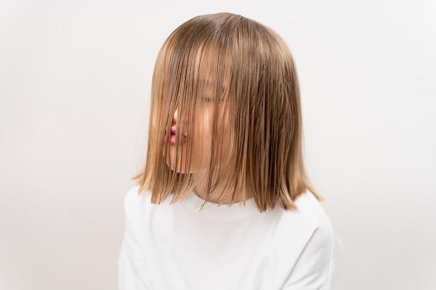 Petite fille drôle et mignonne avec le visage couvert de cheveux sur un fond blanc. shampooing et baume pour enfants. cosmétiques pour filles. brossage léger.