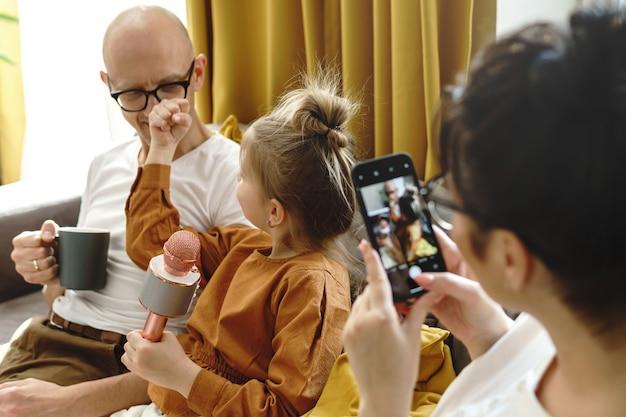 Petite fille drôle montrant le poing à son père pendant la session de karaoké