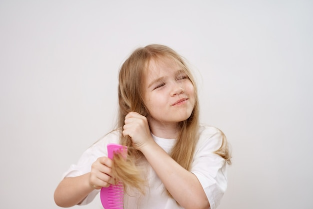 La petite fille drôle peigne les cheveux longs et emmêlés sur un fond blanc. cosmétiques pour le soin des cheveux des enfants.