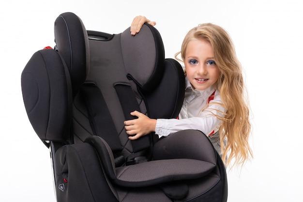 Une petite fille avec du maquillage et des cheveux blonds dans une chemise blanche, des pull-ups rouges, un pantalon dans une cage, des chaussettes rouges et des chaussures avec une chaise bébé.