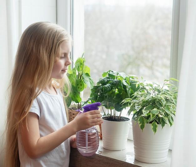Petite fille éclaboussant de l'eau sur les plantes d'intérieur