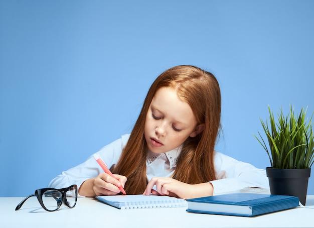 Petite fille écolière enfant fait ses devoirs assis à une table