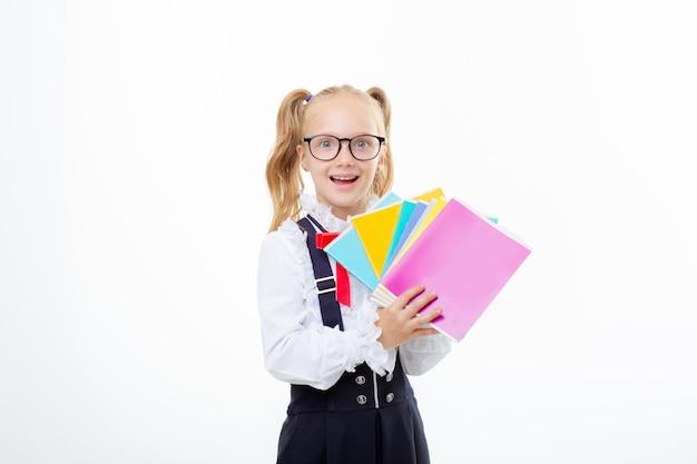 Une petite fille d'écolière tient des cahiers sur un fond blanc d'isolement
