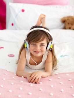 Petite fille écoutant de la musique au lit