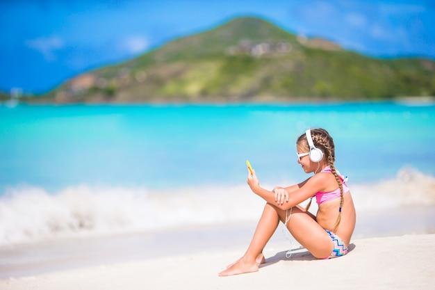 Petite fille écoutant de la musique sur un casque sur la plage des caraïbes