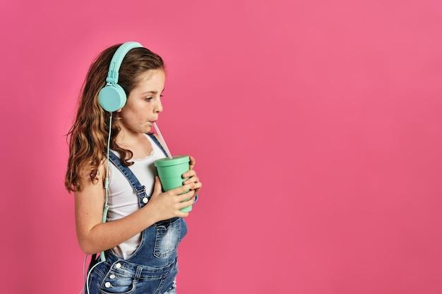 Petite fille écoutant de la musique avec des écouteurs et buvant un jus sur un mur rose