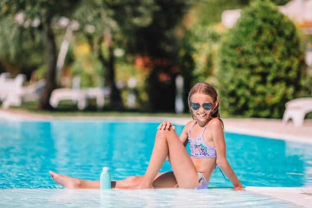 Petite fille avec un écran solaire dans la piscine